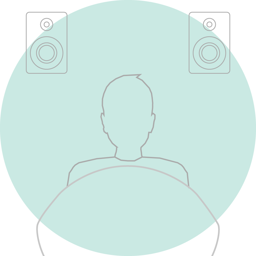 a person sitting on sofa and enjoying ambidio powered sound from two speakers